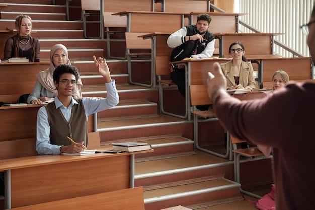 Jonge succesvolle student in brillen en vrijetijdskleding die hand opsteekt terwijl hij aan het bureau op de eerste rij zit en naar de professor kijkt tijdens de les