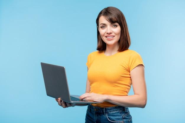 Jonge succesvolle student of zakenvrouw op zoek naar jou tijdens het gebruik van laptop voor huiswerk