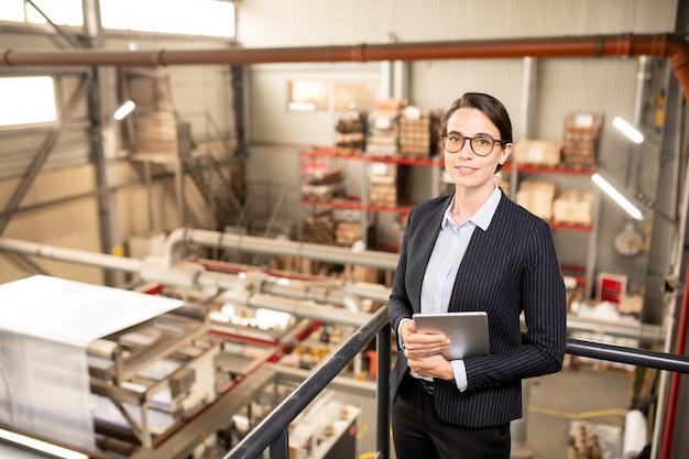 Jonge succesvolle technische manager in formalwear op zoek naar jou tijdens het werken in het magazijn van industriële installaties