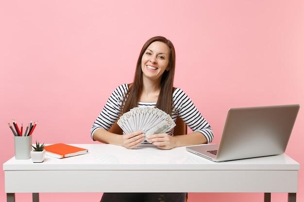 Jonge succesvolle vrouw in vrijetijdskleding die veel dollars contant geld vasthoudt terwijl ze zit, op kantoor werkt met pc-laptop