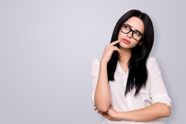 Jonge succesvolle vrouw met bril heeft een nieuw idee en denkt erover na. ze kijkt opzij op de kopie ruimte