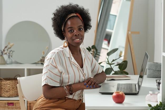 Jonge succesvolle vrouw zit aan bureau voor laptop
