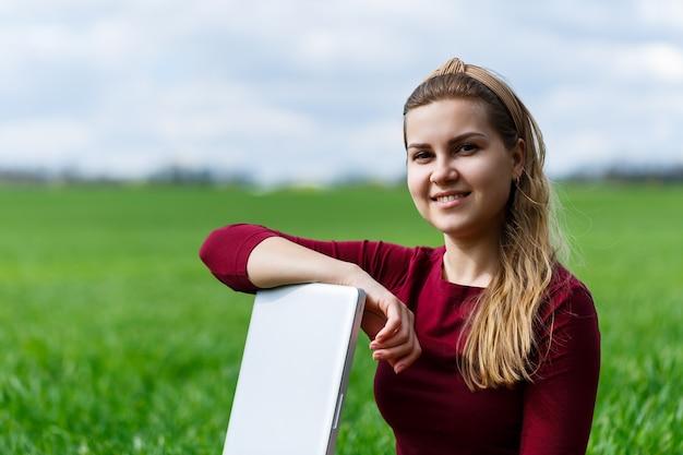 Jonge succesvolle vrouw zit op groen gras met een laptop in haar handen. rust na een goede werkdag. werk aan de natuur. studentenmeisje dat op een afgelegen plek werkt. nieuwe zakelijke ideeën
