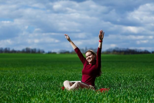 Jonge succesvolle vrouw zit op groen gras met een laptop in haar handen. rust na een goede werkdag. werk aan de natuur. studentenmeisje dat op een afgelegen plek werkt. werkplek in de natuur