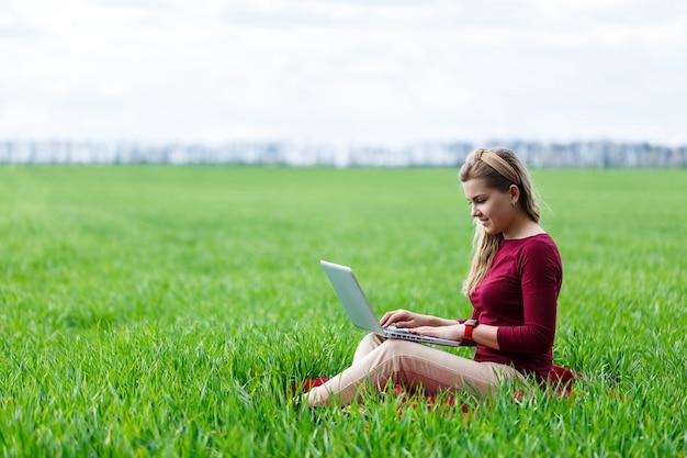 Jonge succesvolle vrouw zit op groen gras met een laptop in haar handen. werk aan de natuur. studentenmeisje dat op een afgelegen plek werkt. nieuwe zakelijke ideeën