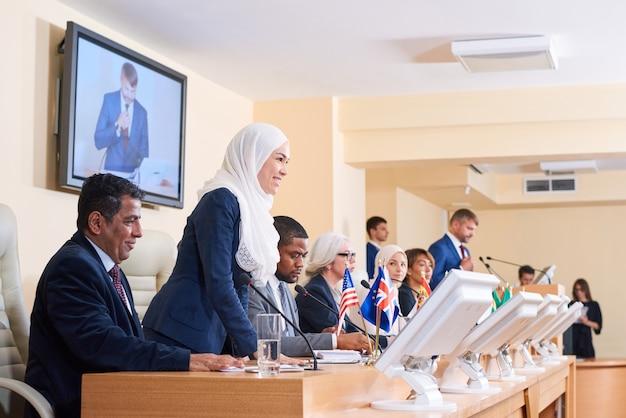 Jonge succesvolle vrouwelijke moslimafgevaardigde in formalwear en hijab die een van de collega's bekijkt terwijl hij vraag stelt