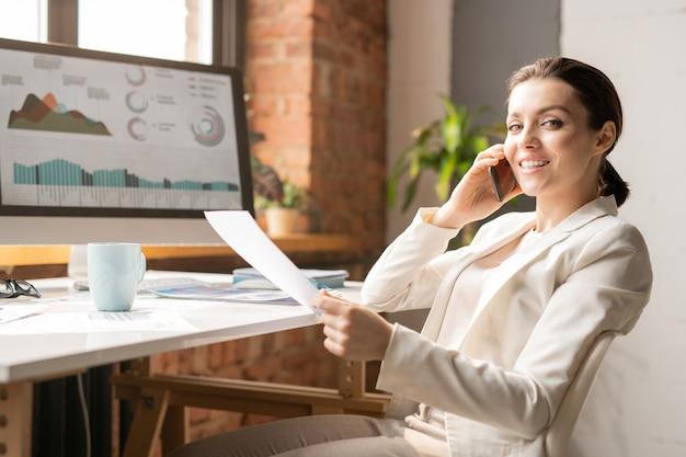 Jonge succesvolle vrouwelijke regisseur of ceo in elegant pak op zoek naar jou met een glimlach tijdens het gesprek aan de telefoon tijdens het werk