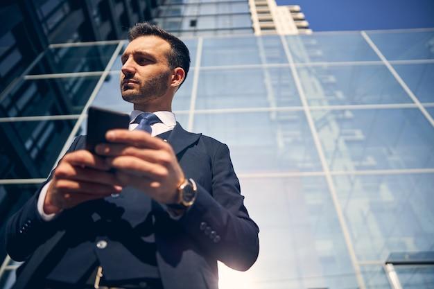 Jonge succesvolle zakenman die buiten in pak met stropdas blijft terwijl hij smartphone in zijn handen houdt