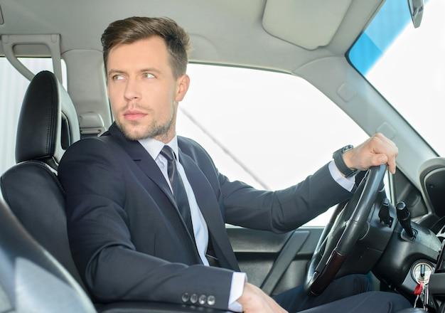 Jonge succesvolle zakenman die in de auto berijdt.