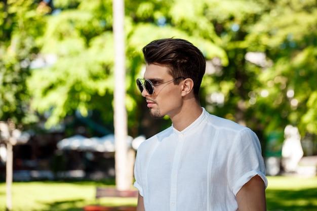 Jonge succesvolle zakenman die in zonnebril zonnige stad rondwandelen