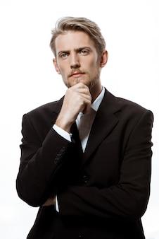 Jonge succesvolle zakenman die met hand op kin denkt
