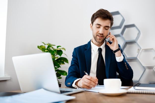 Jonge succesvolle zakenman die op telefoon, bureauachtergrond spreekt.