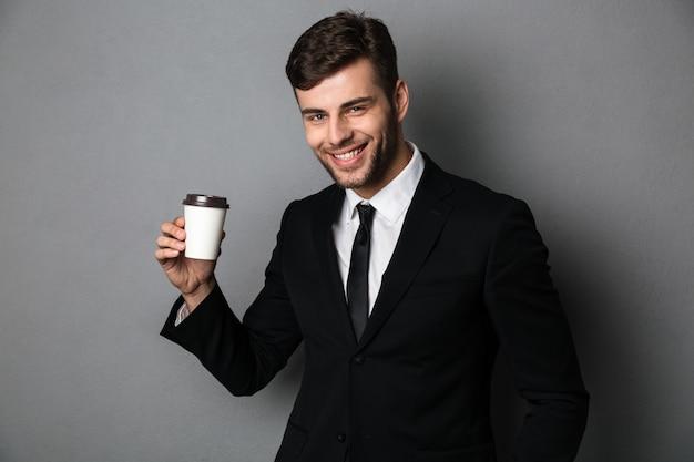 Jonge succesvolle zakenman die zijn ochtendkoffie enjoing,