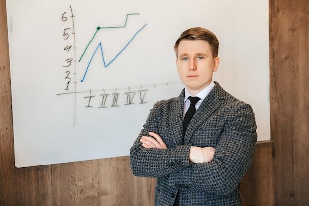 Jonge succesvolle zakenman en kantoormedewerker staat tegen een schoolbord met een grafiek en presenteert een nieuw project van ideeën voor een succesvol businessplan