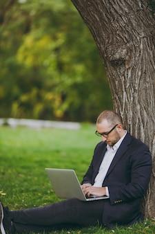 Jonge succesvolle zakenman in wit overhemd, klassiek pak, bril. man zit op gras, werk op laptop pc-computer in stadspark op groen gazon buiten op de natuur. mobiel kantoor, bedrijfsconcept.