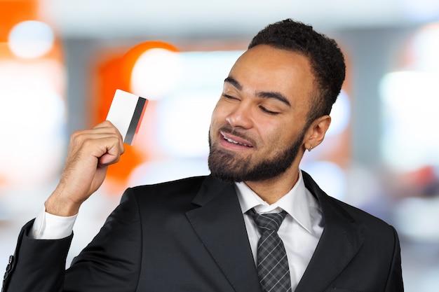 Jonge succesvolle zakenman man in een stijlvol zwart klassiek pak met een plastic creditcard