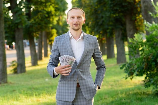 Jonge succesvolle zakenman toont geld in zijn hand.
