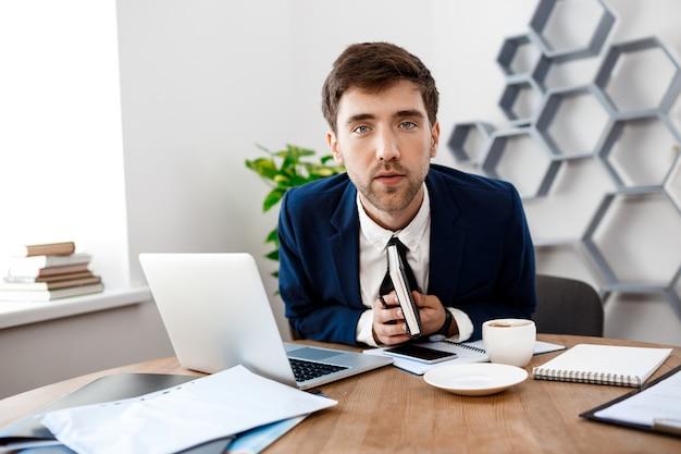 Jonge succesvolle zakenmanzitting op werkplaats, bureauachtergrond.