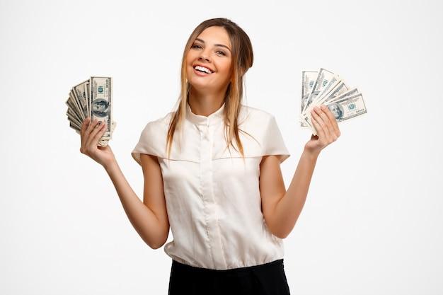 Jonge succesvolle zakenvrouw aanhouden van geld op witte achtergrond.