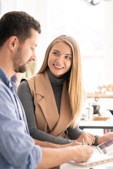 Jonge succesvolle zakenvrouw collega kijken terwijl u luistert naar zijn idee tijdens discussie op werkvergadering