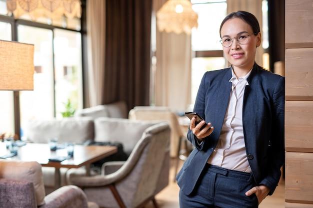 Jonge succesvolle zakenvrouw in formalwear op zoek naar jou tijdens het scrollen in de mobiele telefoon in het restaurant