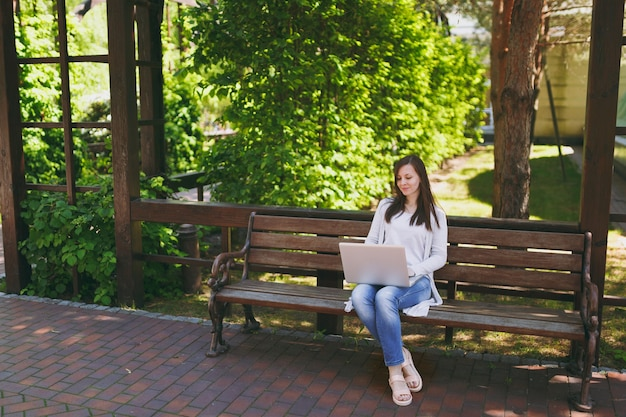 Jonge succesvolle zakenvrouw in lichte vrijetijdskleding. vrouw zittend op een bankje bezig met moderne laptop pc-computer in stadspark in straat buiten op de natuur. mobiel kantoor. freelance bedrijfsconcept