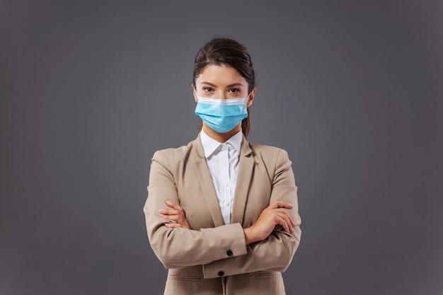 Jonge succesvolle zakenvrouw met beschermend gezichtsmasker staande met gekruiste armen tijdens de uitbraak van het coronavirus.