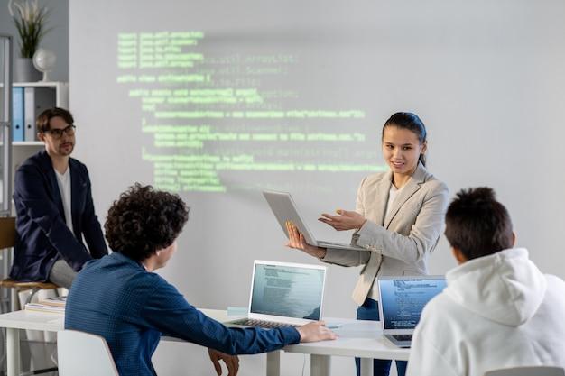 Jonge succesvolle zakenvrouw wijzend op laptopvertoning tijdens het uitleggen van gegevens aan collega's tijdens de presentatie van haar project