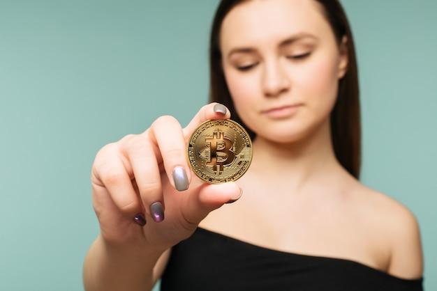 Jonge succesvolle zelfverzekerde vrouw houdt een gouden bitcoin in haar hand