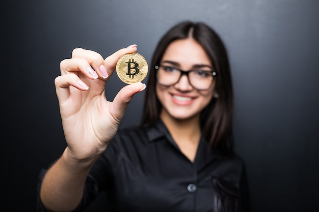 Jonge succesvolle zelfverzekerde vrouw met bril houdt een gouden bitcoin in haar hand geïsoleerd op zwarte muur