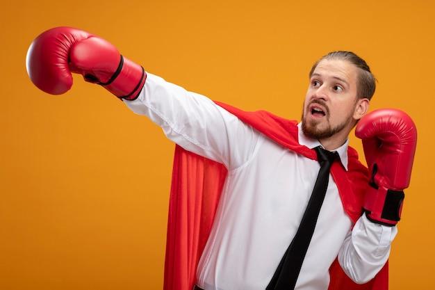 Jonge superheld kerel die stropdas en bokshandschoenen draagt ?? die naar kant kijkt die hand aan kant houdt die op oranje wordt geïsoleerd