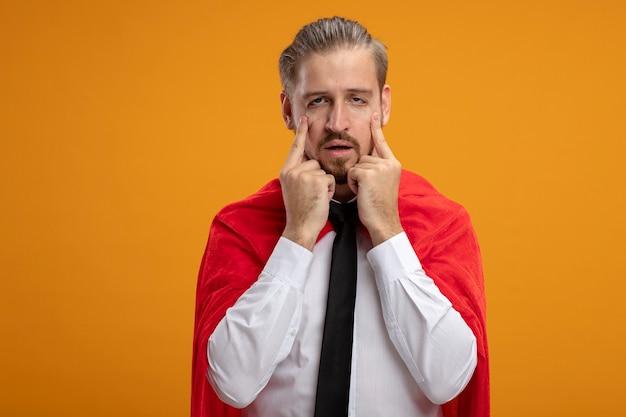 Jonge superheld man dragen stropdas kijken camera doen met vingers aziatische ogen geïsoleerd op een oranje achtergrond