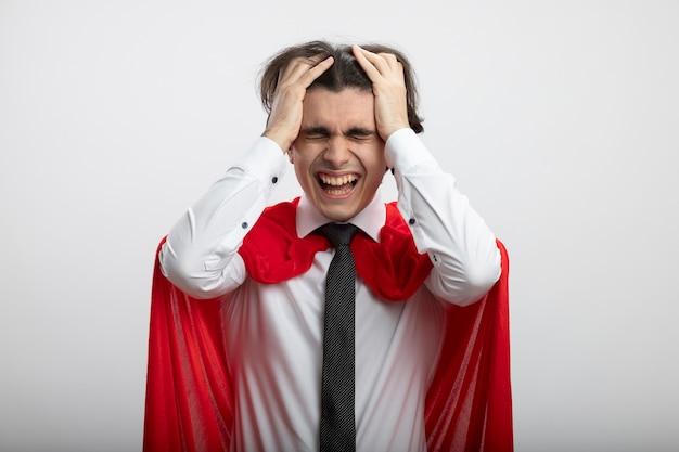 Jonge superheld man lachen met gesloten ogen dragen stropdas pakte hoofd geïsoleerd op een witte achtergrond