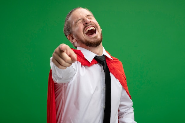 Jonge superheld man lachen met gesloten ogen tonen je gebaar geïsoleerd op een groene achtergrond