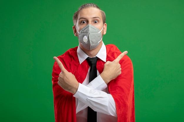 Jonge superheld man met medische masker en stropdas punten aan verschillende kanten geïsoleerd op groen