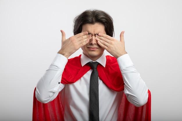 Jonge superheld man met stropdas bedekte ogen met handen geïsoleerd op wit