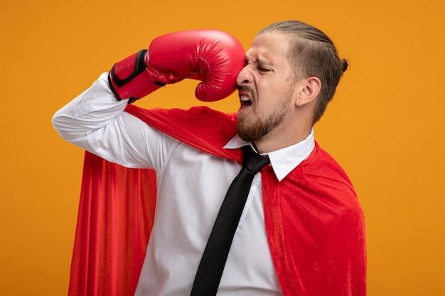 Jonge superheld man met stropdas en bokshandschoenen die zichzelf verslaan geïsoleerd op een oranje achtergrond