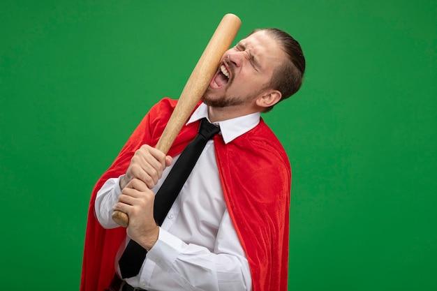 Jonge superheld man slaat zichzelf met een honkbalknuppel geïsoleerd op groen