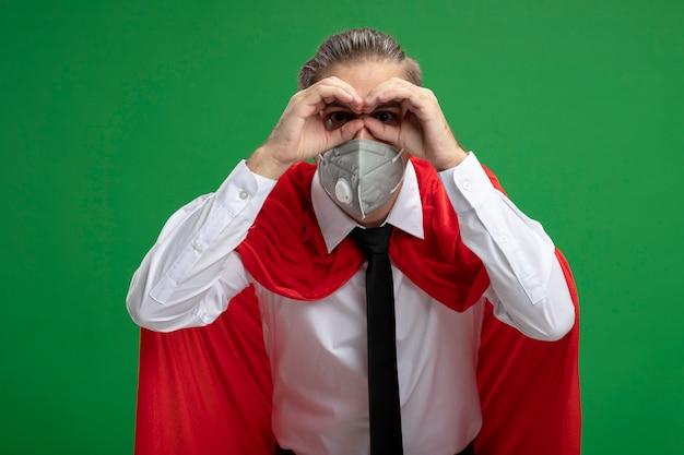Jonge superheldenker die medisch masker en stropdas dragen die blikgebaar tonen dat op groene achtergrond wordt geïsoleerd