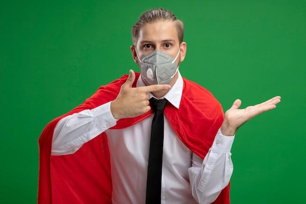 Jonge superheldenkerel die medisch masker en stropdas draagt die doen alsof hij vasthoudt en wijst naar iets dat op groen wordt geïsoleerd