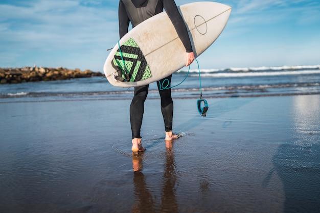 Jonge surfer die het water ingaat met zijn surfplank in een zwart surfpak