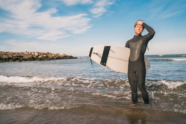 Jonge surfer die zich in de oceaan met zijn surfplank in een zwart surfpak bevindt. sport en watersport concept.