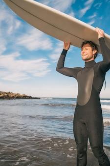 Jonge surfer die zijn surfplank steunt.