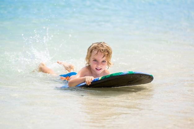 Jonge surfer, gelukkige jonge jongen in de oceaan op surfplank
