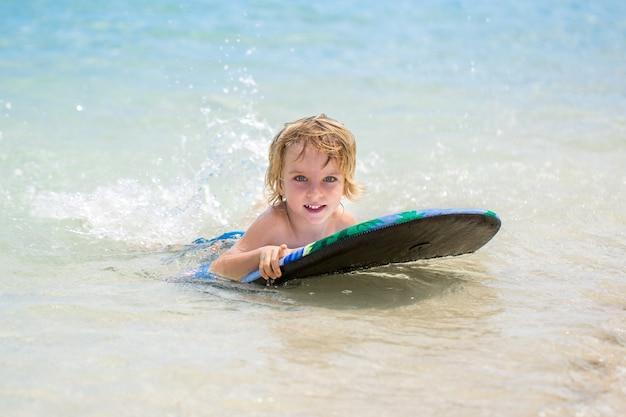 Jonge surfer gelukkige jonge jongen in de oceaan op surfplank