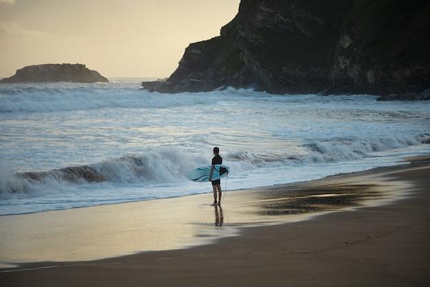 Jonge surfer in kort wetsuit met funboard in de hand blijft bij zonsopgang alleen op het verborgen surfstrand. klaar om de oceaan in te gaan