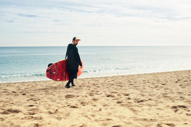 Jonge surfer man op strand met surfplank