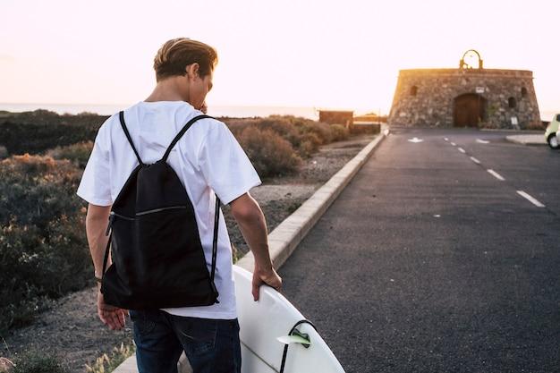 Jonge surferjongen die tijdens zonsondergang op de weg naar de oceaan loopt met surfplank