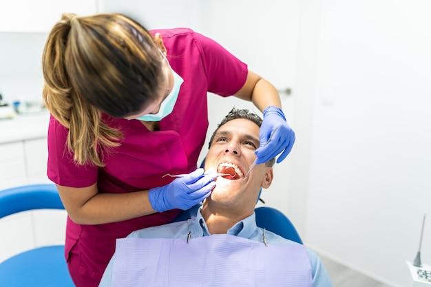 Jonge tandartsvrouw die een controle tot een patiënt doet.