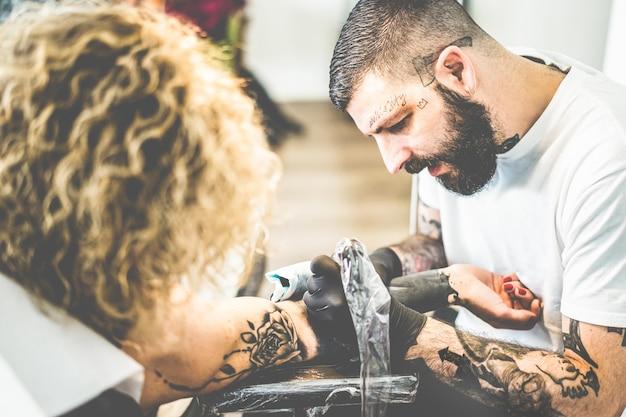 Jonge tatoeëerder werken in zijn creatieve studio van inkt